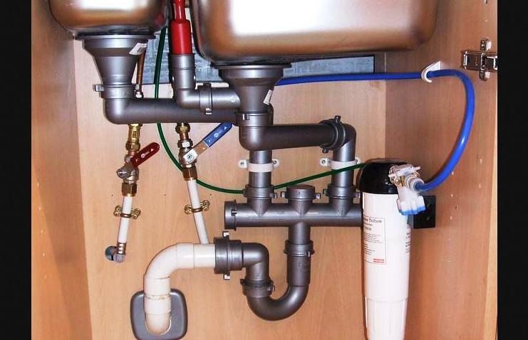 Vízvezetékek és lefolyóvezetékek a konyhai mosogató alatt.